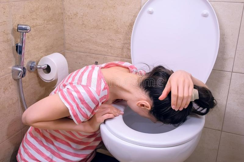 Drunk tired woman is vomiting in toilet sitting on the floor at home, hangover, side view. Drunk tired woman is vomiting in toilet sitting on the floor at home stock photo