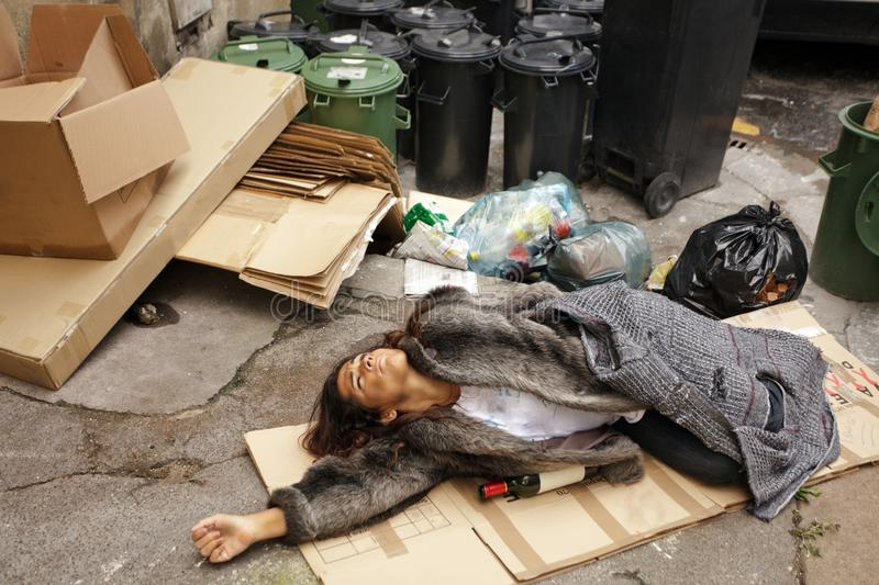 Drunk tramp woman in trash royalty free stock photography
