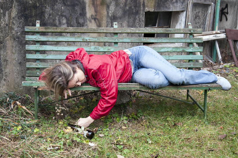 Drunk woman. Young woman in a red jacket lying on a bench by derelict house apparently drunk and asleep; concept for alcoholism, homelessness and social problems stock image