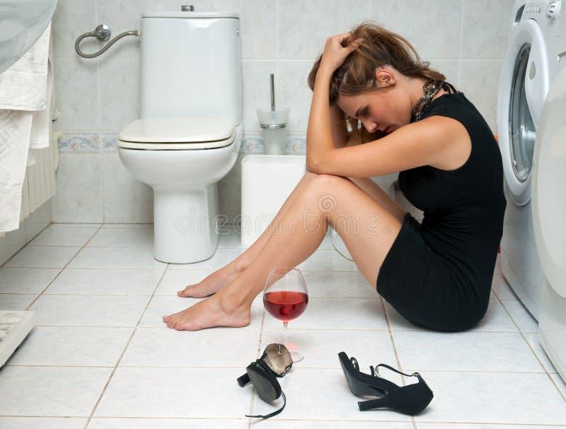 Drunk woman in her bathroom stock image