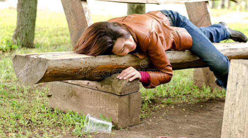 Drunk woman sleeping it off on a wooden bench royalty free stock photo