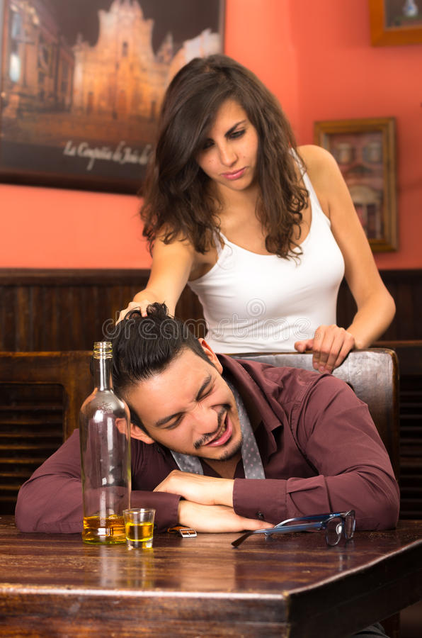 Drunk young man and angry girlfirend in a bar stock photo
