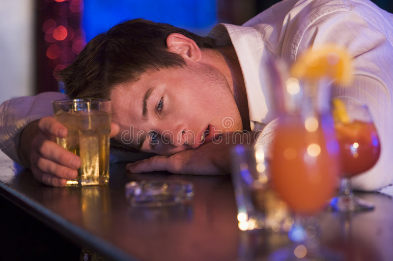 Drunk young man resting head on bar counter. Looking depressed royalty free stock photos