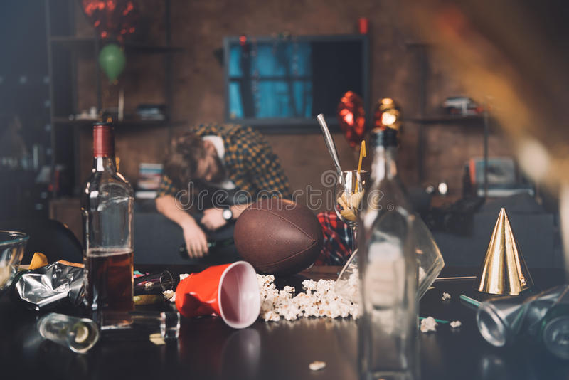 Drunk young man sleeping on couch in messy room stock images