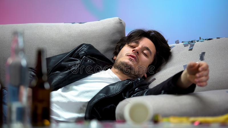 Drunk young man sleeping on couch after night long party, idle life, hangover. Stock photo stock photos