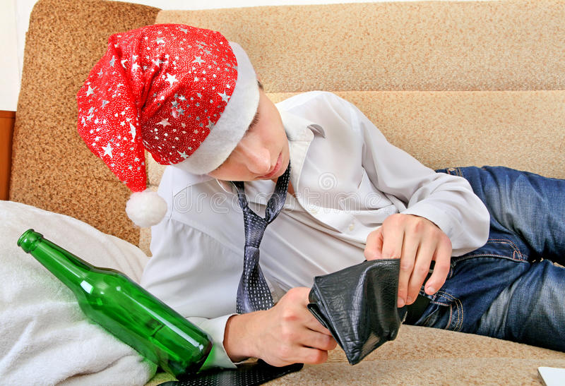 Drunken Teenager in Santa Hat. Teenager in Santa Hat Checking Empty Wallet after Party on the Sofa stock photo