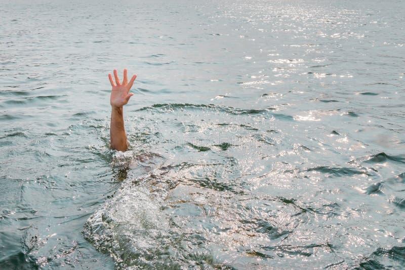 Drunkna mannen som frågar för hjälp Klibba handen ut ur vatten royaltyfria bilder