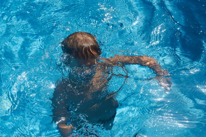 Drunkna ungen in i simbassängvatten pojke royaltyfri foto
