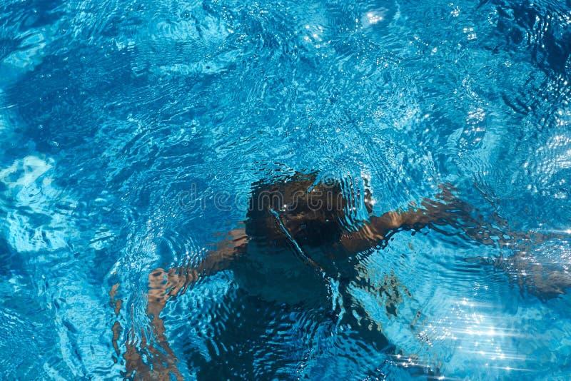 Drunkna ungen in i simbassängvatten pojke arkivbild
