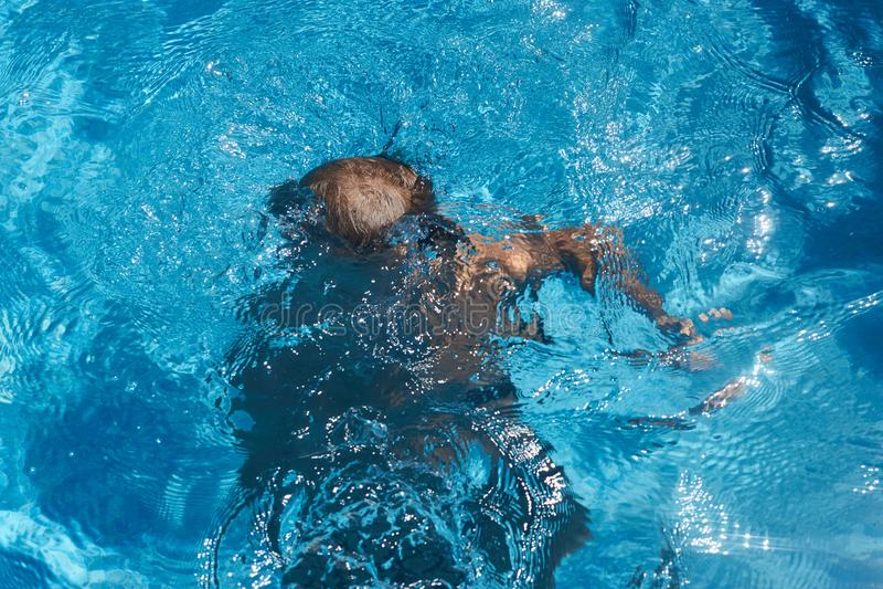 Drunkna ungen in i simbassängvatten pojke arkivfoton