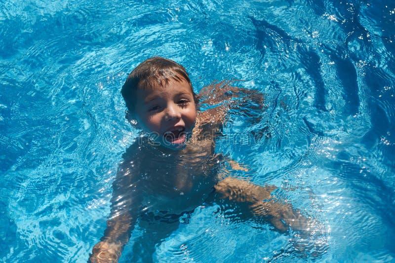 Drunkna ungen in i simbassängvatten Ung pojke royaltyfri foto