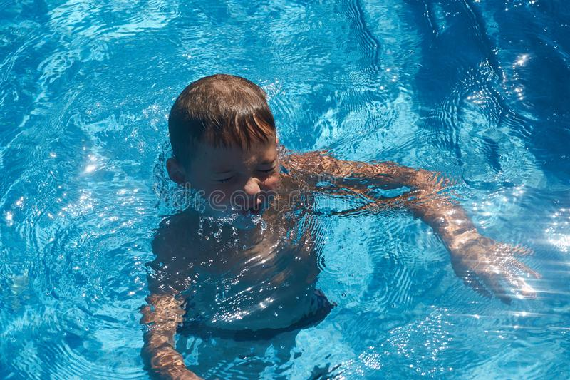 Drunkna ungen in i simbassängvatten Ung pojke arkivfoton