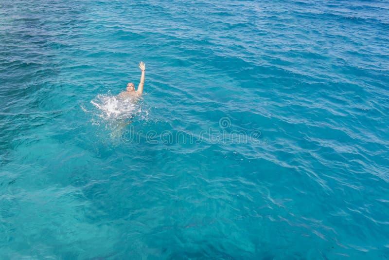 Drunkningman i havet som frågar för hjälp med lyftta armar Mannen drunknar i havet arkivbild