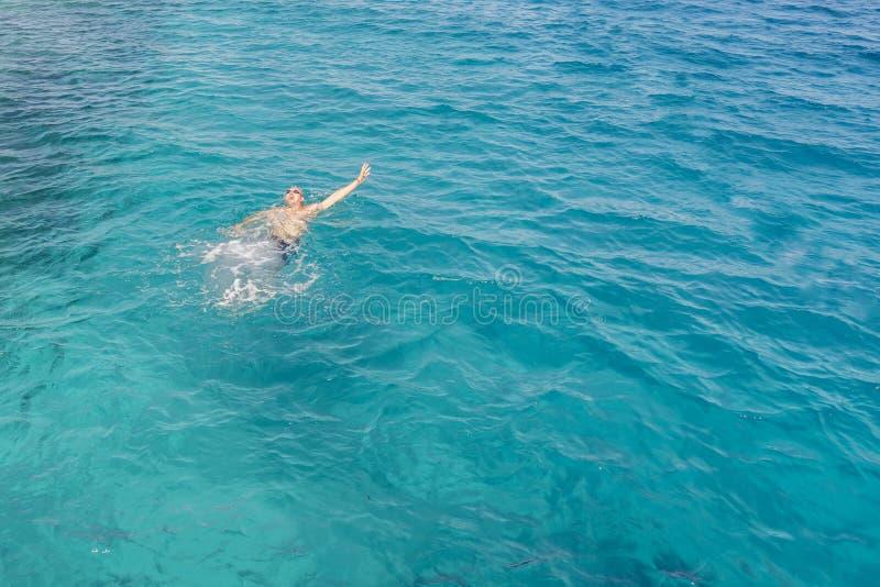 Drunkningman i havet som frågar för hjälp med lyftta armar Mannen drunknar i havet royaltyfri fotografi