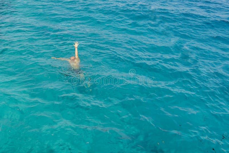 Drunkningman i havet som frågar för hjälp med lyftta armar Mannen drunknar i havet man som drunknar i havet och den vinkande hand royaltyfria foton