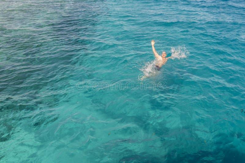Drunkningman i havet som frågar för hjälp med lyftta armar Mannen drunknar i havet man som drunknar i havet och den vinkande hand royaltyfri foto