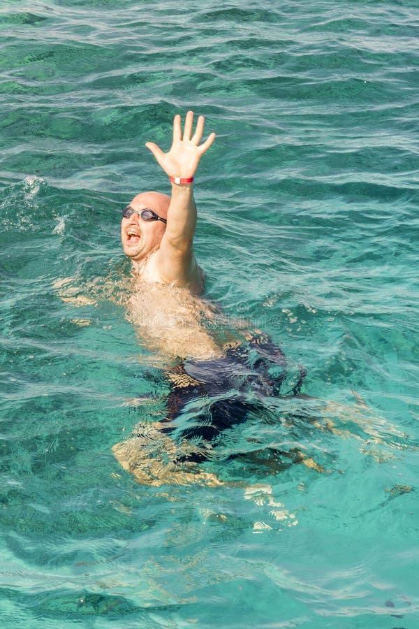 Drunkningman i havet som frågar för hjälp med lyftta armar Mannen drunknar i havet Vertikalt foto stock illustrationer