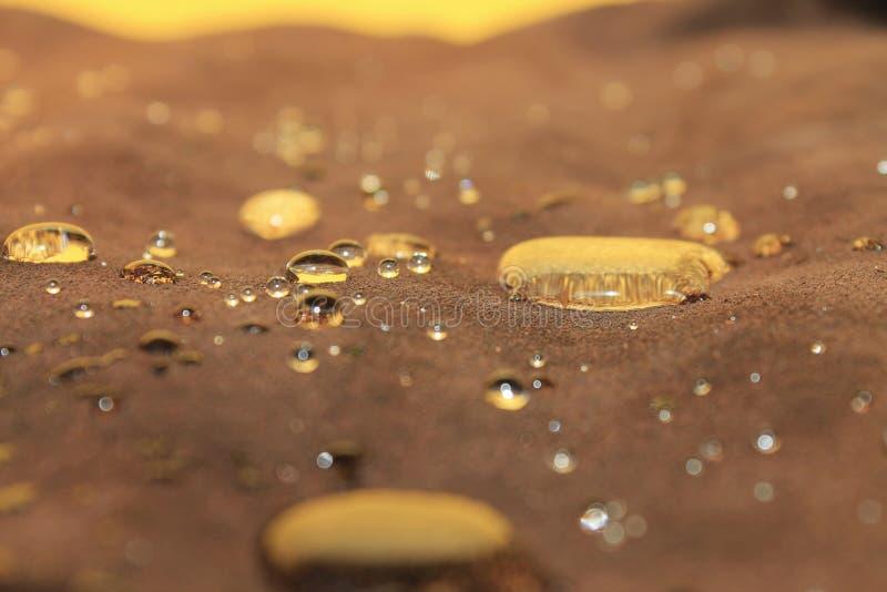 Druppels water op de bruine suede die de gele wand weerkaatst stock afbeeldingen