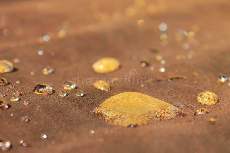 Druppels water op de bruine suede die de gele wand weerkaatst stock afbeelding