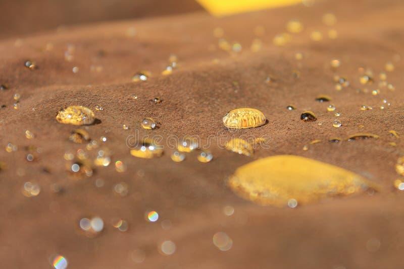Druppels water op de bruine suede die de gele wand weerkaatst royalty-vrije stock foto