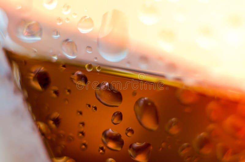 Druppeltjes op het glas van de cognac Abstracte hellende horizon De macro unfocussed blured achtergrond stock fotografie