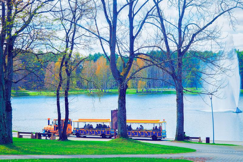 Druskininkai, Lithuania - April 30, 2017: Excursion train with tourists, water fountain on Druskonis Lake and the nature in. Druskininkai, Lithuania. Toned stock photography