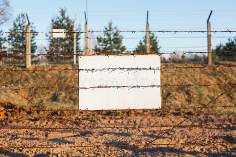 Drutu kolczastego ogrodzenie ochrania niebezpiecze?stwo stref? Bielu znaka deska zdjęcia royalty free