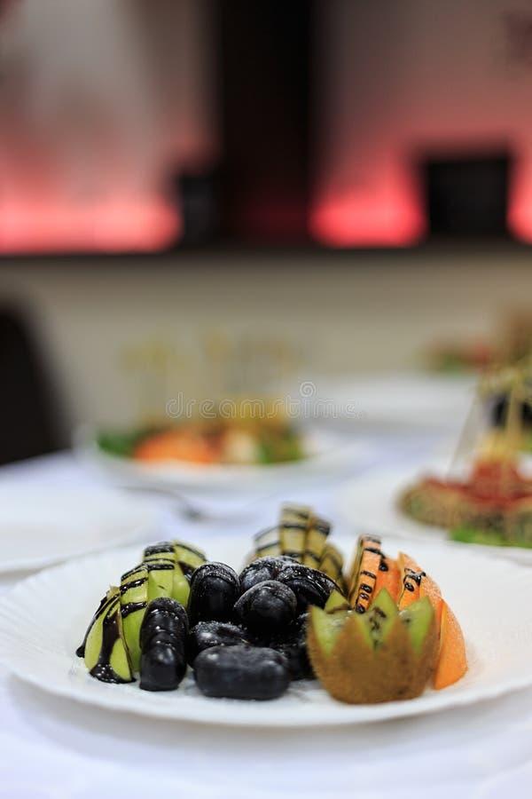 Druvor äpple, päron, apelsin, kiwi som skivas och täckas av choklad och sockertoppning royaltyfri foto