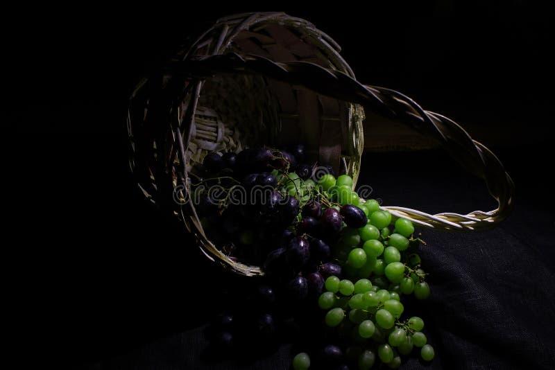 Druvor i en korg på en mörk bakgrund, closeup arkivbild