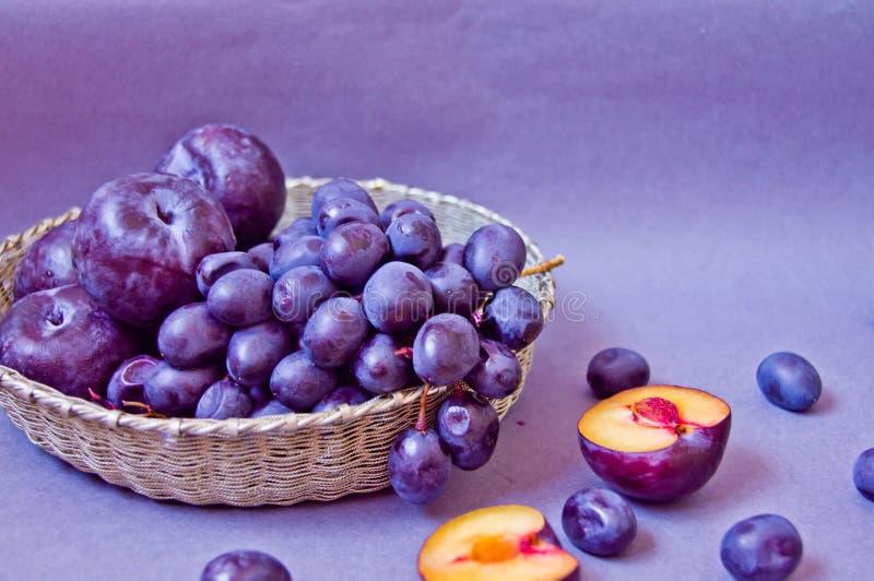 Druvor och plommoner i en silverkorg på en grå bakgrund fotografering för bildbyråer