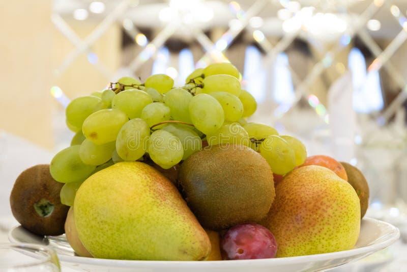 Druvor päron, kiwi, plommon, äpple i en platta Uppläggningsfat för efterrättfrukt Tabellinbrott en restaurang eller ett kafé royaltyfria foton