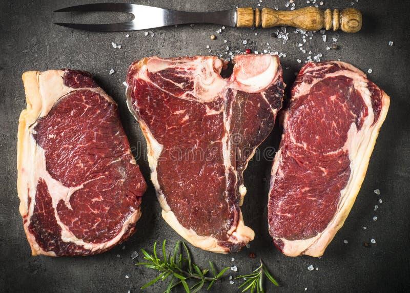 Dry aged beef steaks - ribeye, striploin, t-bone steaks on Black. Slate background. Top view stock photo