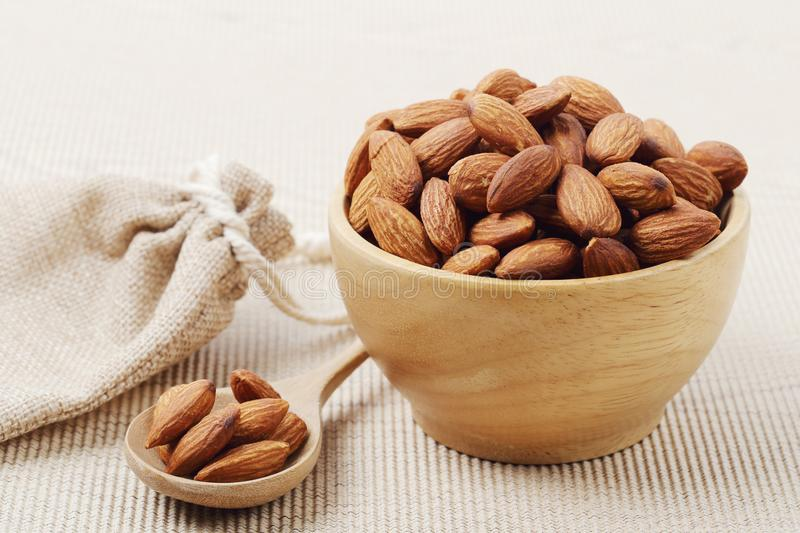Almonds nuts in a wooden bowl over corrugated paper royalty free stock photo