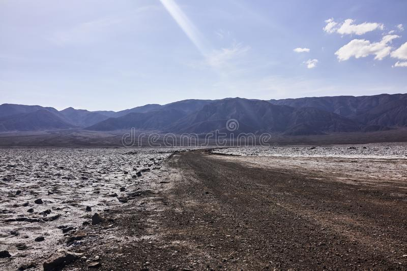 Dry Arid Desert Terrain and Mountains in the Distance. In the Atacama desert in Chile. A beam of sunlight touches the dry surface royalty free stock photography