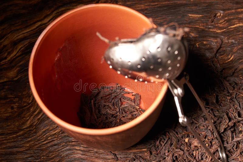 dry black chinese tea set,with strainer closeup,cups and teapot on background over old wood board royalty free stock image