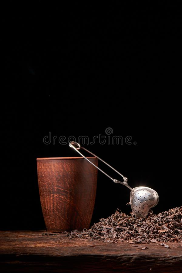 dry black chinese tea set,with strainer closeup,cups and teapot on background over old wood board royalty free stock images