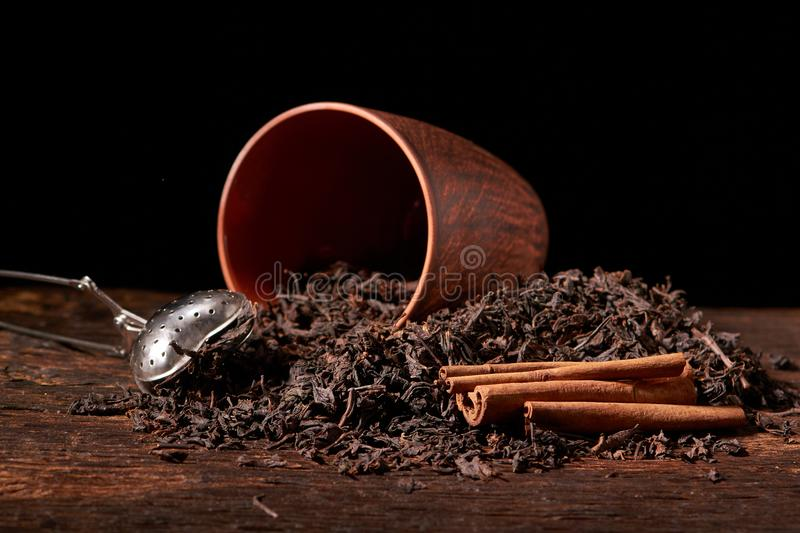 dry black chinese tea set,with strainer closeup,cups and teapot on background over old wood board stock image