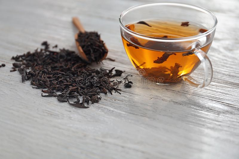 Dry black tea leaves and cup of aromatic beverage on table royalty free stock photography