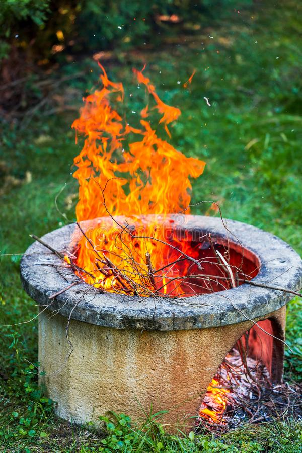 Free Dry Branches Burn In Isolated Campfire Pit In The Garden. High Bright Flames Flickering On Open Garden Fire Pit Stock Image - 141219071