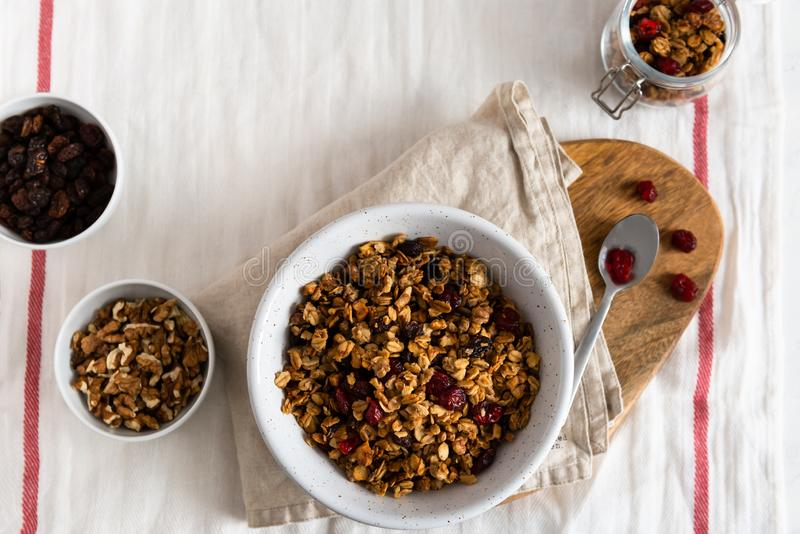Dry breakfast cereals. Crunchy honey granola bowl with flax seeds, cranberries and coconut. Healthy, vegeterian fiber food. royalty free stock photo
