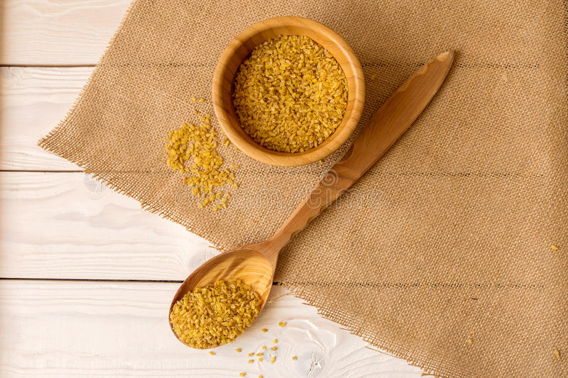 Dry bulgur wheat in wood bowl with spoon on the table stock photos
