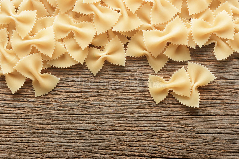 Dry butterfly pasta on a wooden background. bow tie pasta. royalty free stock image