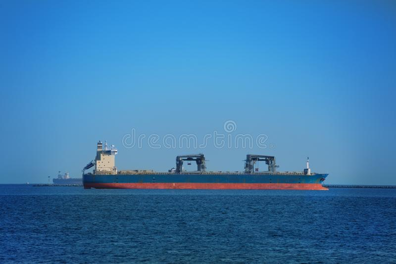 Dry cargo ship in the open sea with many containers royalty free stock image