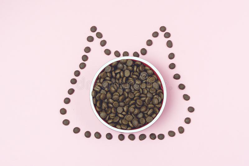 Dry Cat Food in Bowl on Pink Background Cats Food in Shape of Kitten Top View Horizontal Modern Food Comcept for Cats stock photo