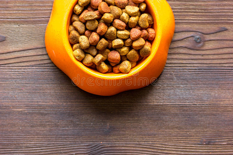 Dry cat food in bowl on wooden background top view.  stock image
