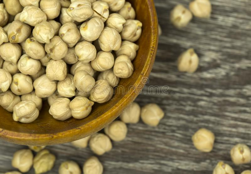 Dry chickpeas close up in a wooden spoon on a backgroun.  royalty free stock image