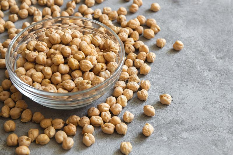 Dry chickpeas in a glass bowl on a gray background royalty free stock images