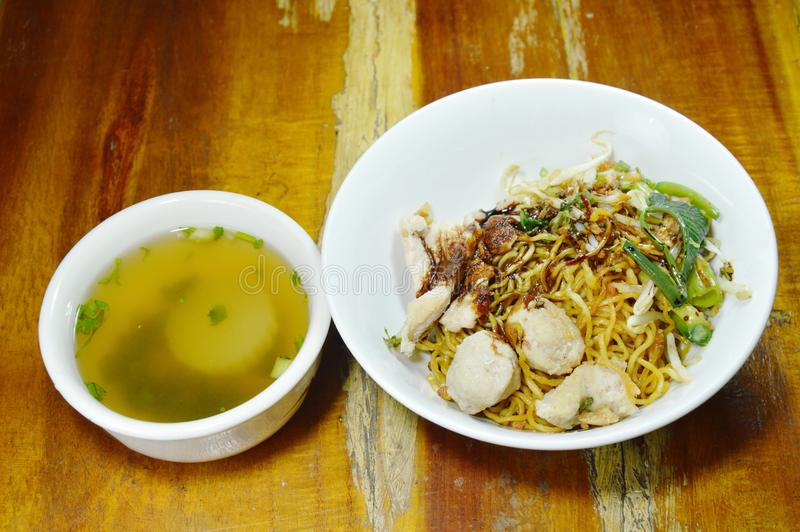Dry Chinese egg noodles topping slice pork and ball dressing sweet black soy sauce with soup. Dry Chinese egg noodles topping slice pork and ball dressing sweet royalty free stock images