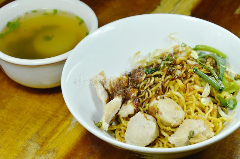 Dry Chinese yellow noodles topping slice pork and ball dressing sweet black soy sauce with soup. Dry Chinese yellow noodles topping slice pork and ball dressing royalty free stock image
