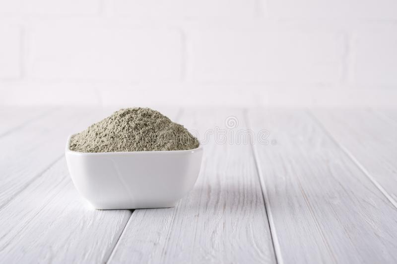 Dry clay powder mask for face and body in ceramic bowl on white royalty free stock image